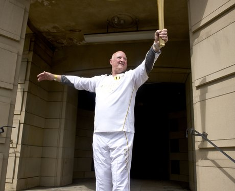 Torchbearer holds Olympic flame with pride