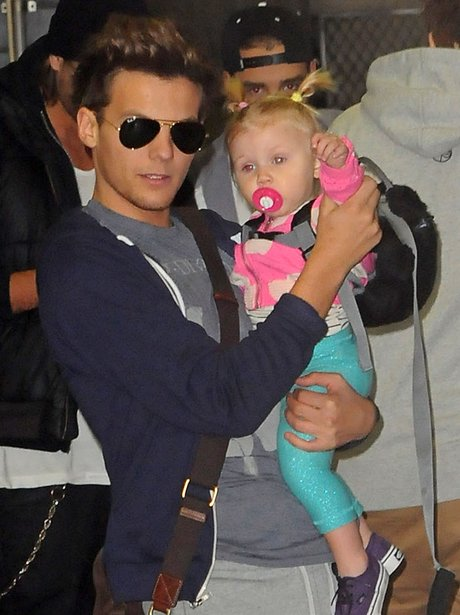 One Direction star Louis Tomlinson holding a baby