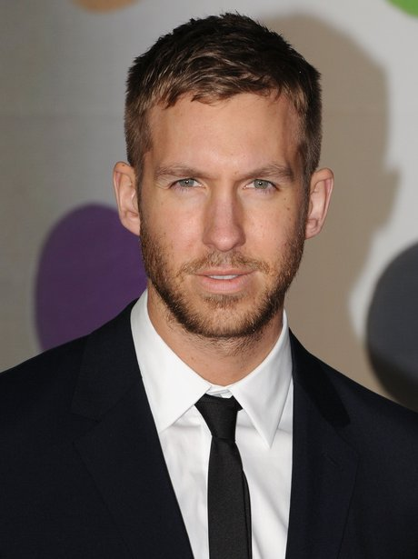 Calvin Harris poses in a black suit