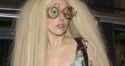 Lady Gaga carrying a guitar and wearing glasses