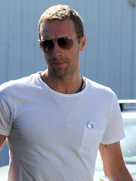 Chris Martin wears a 'Love' pin badge